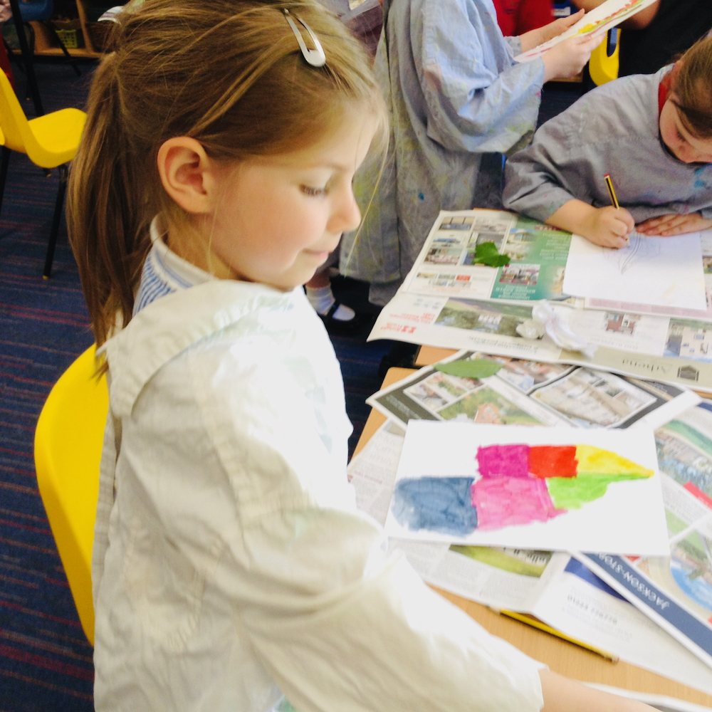 A girl paints a colourful leaf with egg tempera mixing powder paint and egg at Hauxton Primary for Inspire with Pamela Stewart