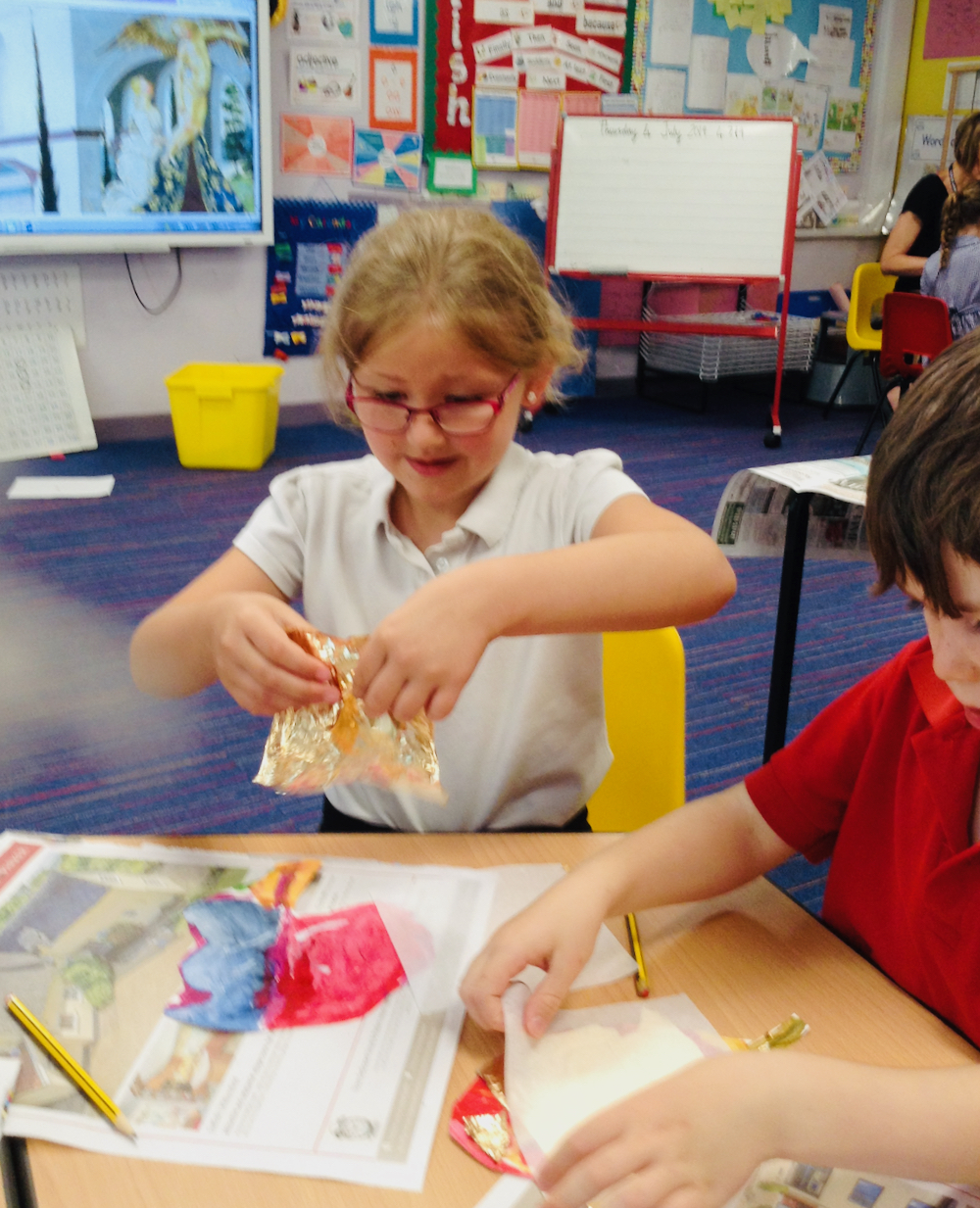 A Year One girl gently rips gold leaf to apply to her brightly painted leaf at Hauxton Primary School for Inspire with Pamela Stewart