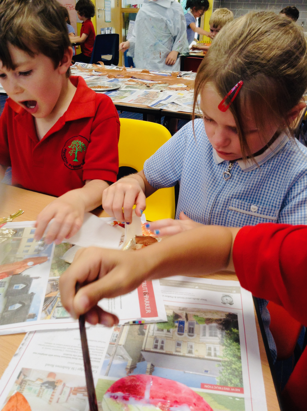 Children apply gold leaf to gild their painted leaves at Hauxton Primary School with Pamela Stewart for Inspire