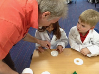 Professor John Love helps children place seeds in petri dishes for a science experiment at Hauxton Primary School
