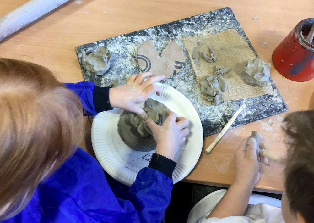 Image of a year one pupil's hands working with grey school clay pushing their thumbs into the damp clay