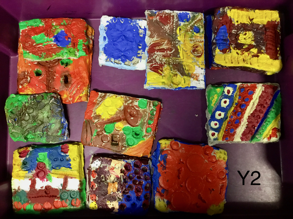 A selection of clay tiles which has been colourfully painted by Year Two Pupils