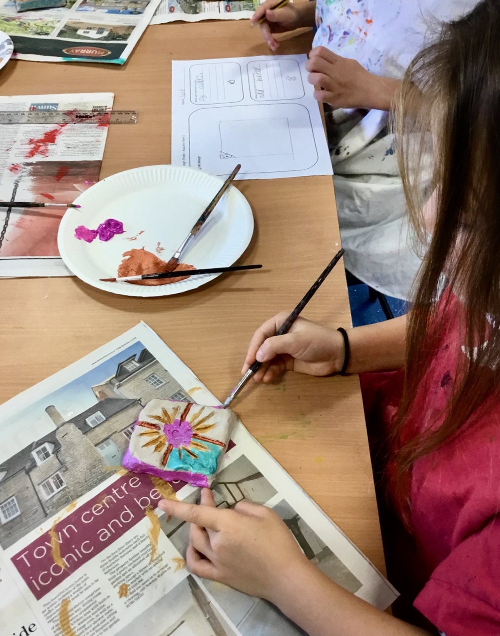 A Year Two Pupil painting with school paint on unfired clay in a classroom taught by Sue Brown