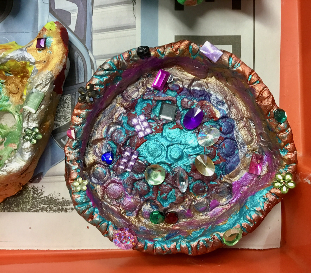 Colourful clay tray decorated with paint and coloured jewels made by a year three pupil