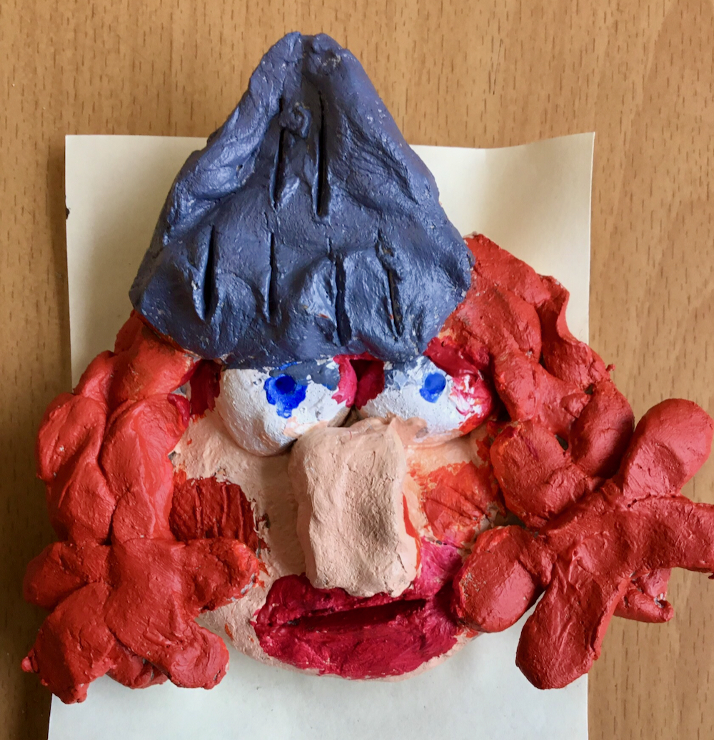 A clay Viking made in clay and painted with orange, curly hair, a large, pink nose, blue eyes and metallic, grey helmet, made by a year four pupil taught by art teacher Sue Brown