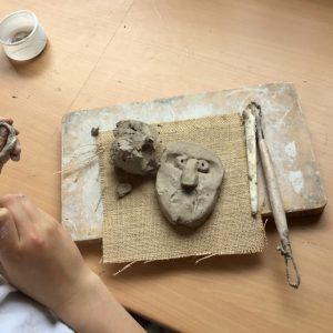 A clay head being created on a school table top by a Year Four pupil with school clay and wooden tools