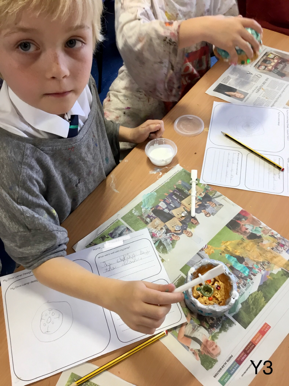 An unknown boy working with glue and paint to decorate a clay pot that he has made with sketchbook pages with his design ideas