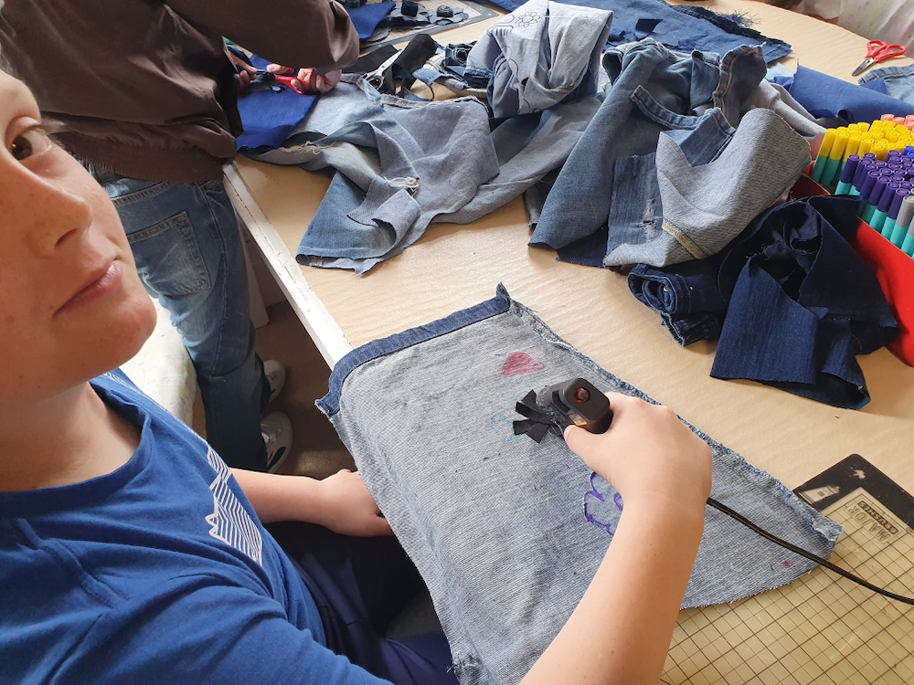 Boy working with a glue gun on discarded jeans part of Inspire project with teacher Natalie Bailey in collaboration with AccessArt and the Fitzwilliam Museum, Cambridge
