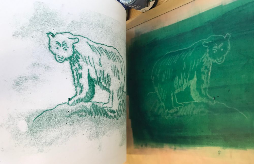 peeling back the paper to reveal the print