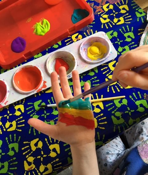 Painting rainbow stripes across hands