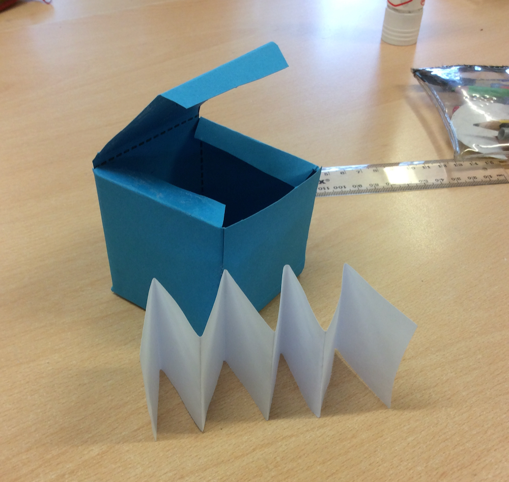 A folded cube and concertina folded paper