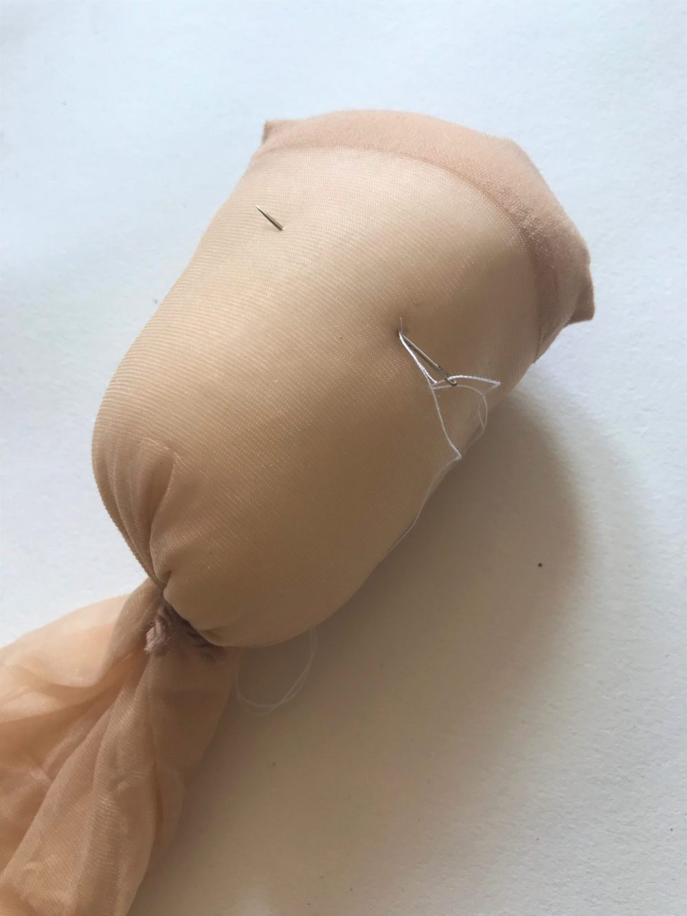 pushing a needle and thread through the stuffed head