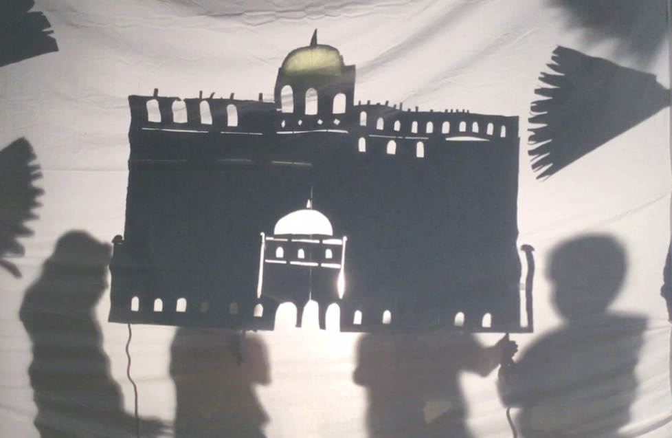Holding up a large shadow puppet of a palace